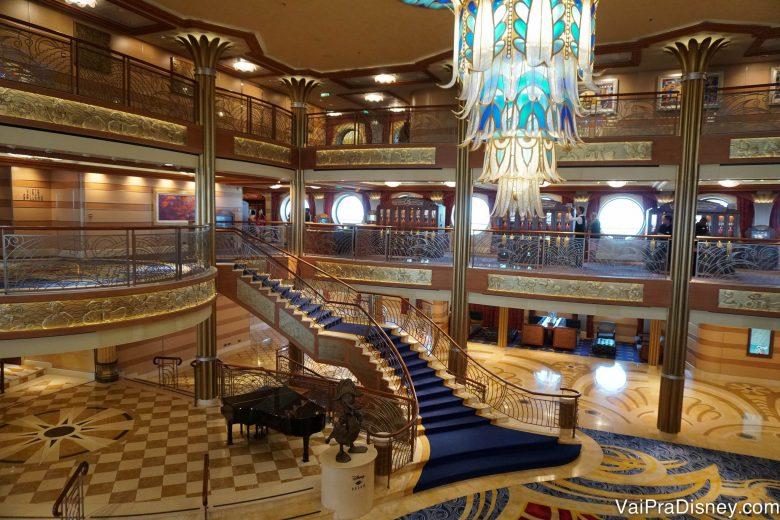 Foto do átrio do Disney Dream, com uma escadaria e um lustre elegantes