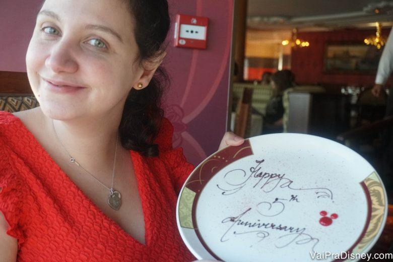 Foto da Renata com o prato que diz Happy Anniversary, cortesia do garçom do navio