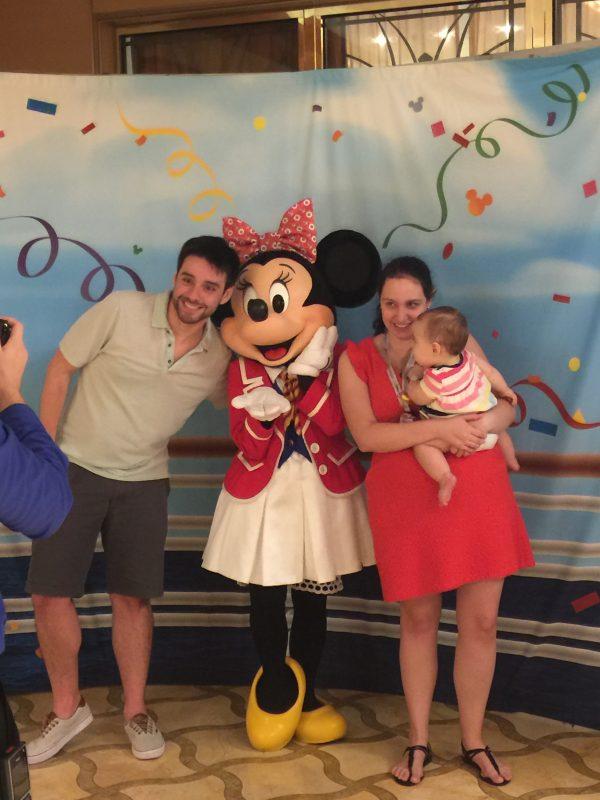 Foto da Renata com a Julia no colo e o Felipe posando para a câmera junto da Minnie