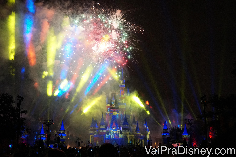 Foto do castelo iluminado em azul com fogos multicoloridos e projeções no céu durante o Happily Ever After