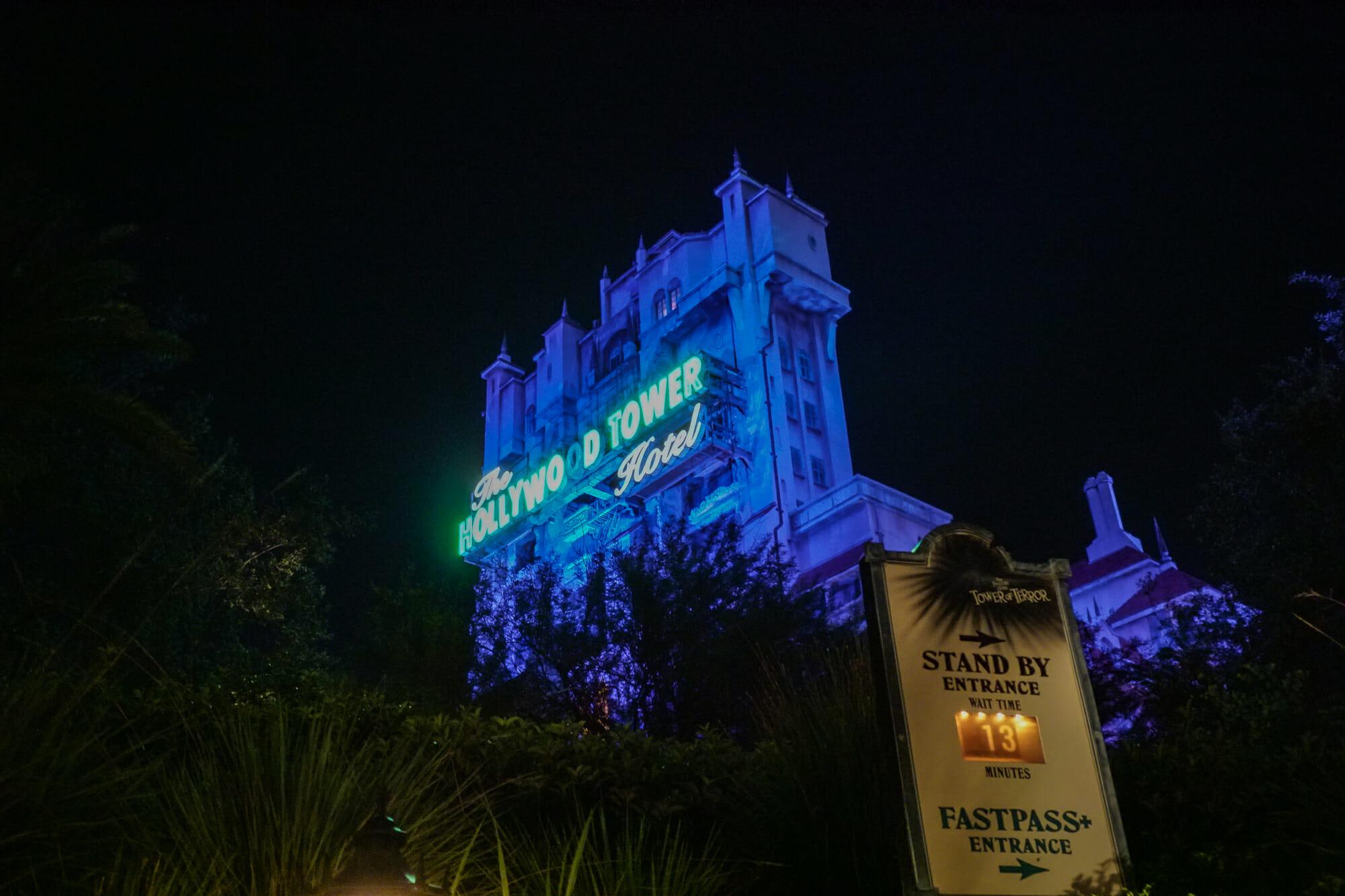 Foto da Tower of Terror, do Hollywood Studios, durante a noite, iluminada em azul com seu nome em verde.
