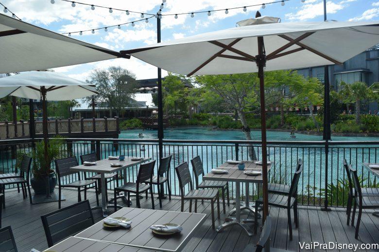 A varanda do restaurante, com mesas, cadeiras e guarda-sóis e vista para o lago de Disney Springs
