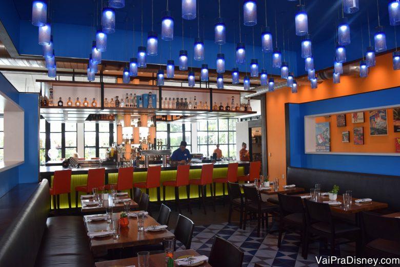 O Frontera Cocina por dentro, com paredes laranjas, teto pintado de azul, muitas luminárias e cadeiras no bar