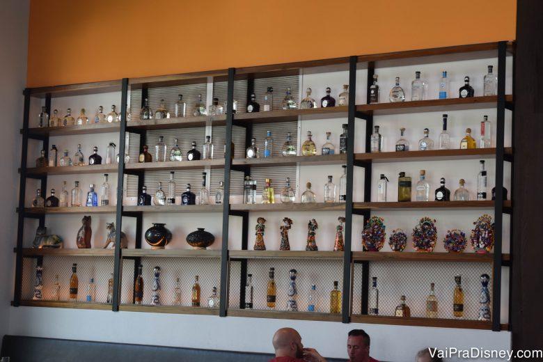 A estante cheia de garrafas e enfeites que decora o Frontera Cocina