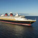 Imagem do navio de cruzeiro da Disney em alto mar. Ele tem detalhes em azul marinho, vermelho, branco e amarelo
