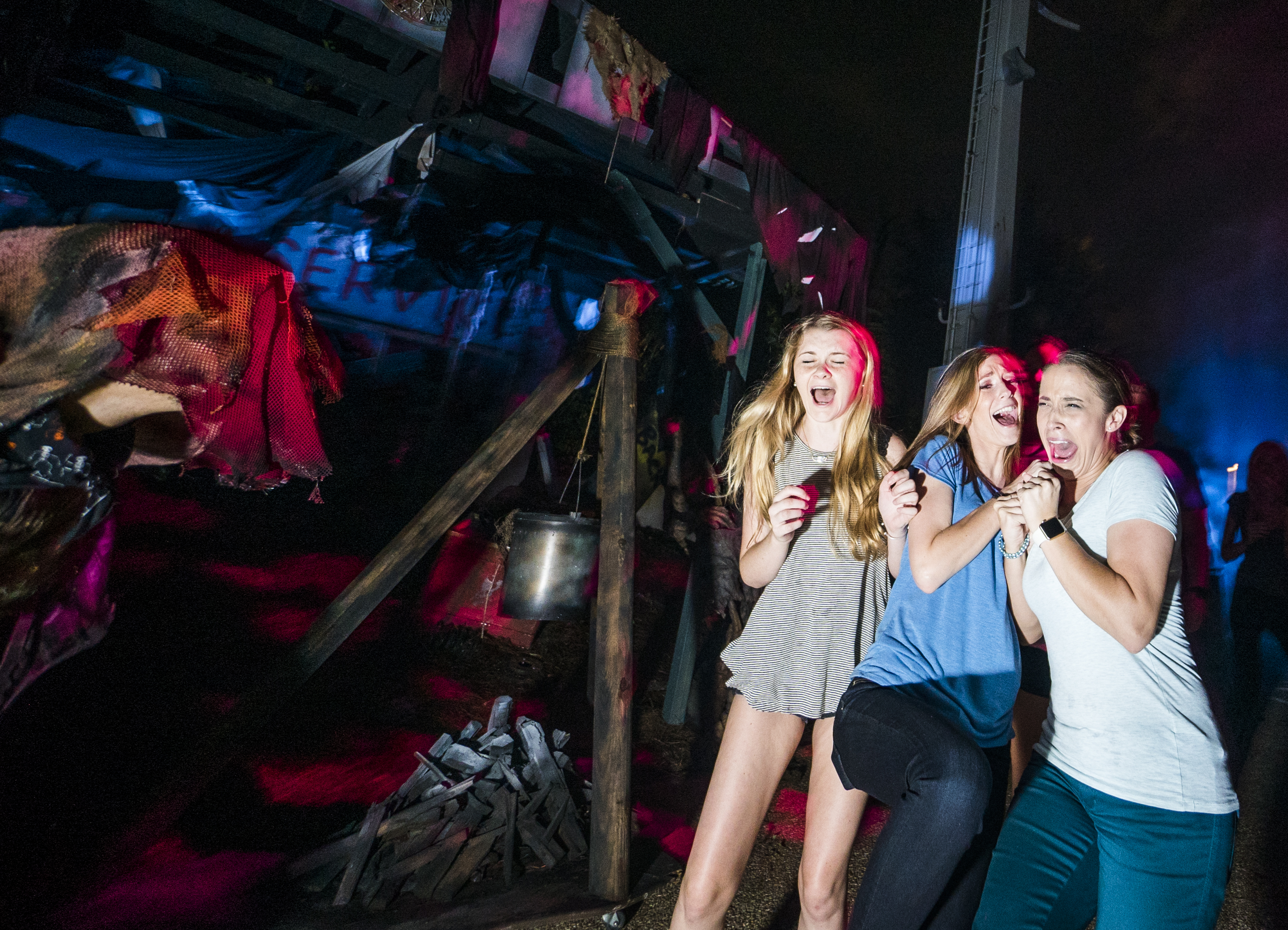 Foto da festa de Halloween do Busch Gardens em que três visitantes estão levando um susto de um personagem indistinto, com a cabeça coberta por um pano.