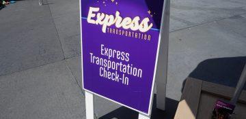 Foto da placa roxa indicando o ponto para embarcar no Express Transportation da Disney