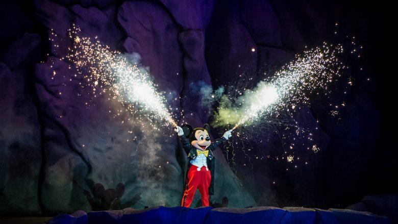 Foto do Mickey durante o Fantasmic, segurando tubos que soltam fogos de artifício.