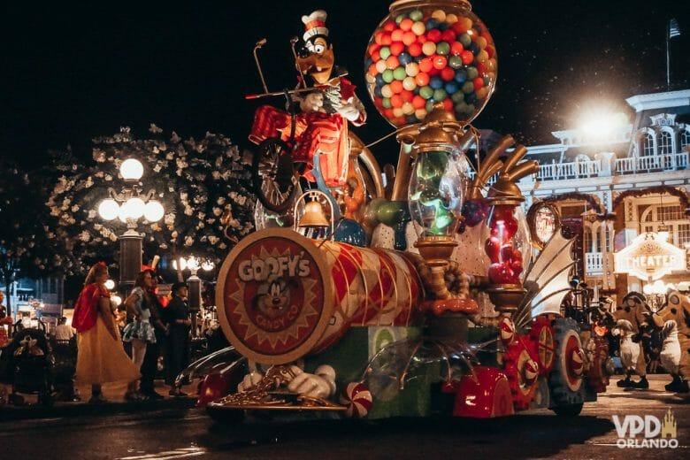 Imagem de um dos carros da parada de Halloween, com o Pateta em cima.  Há um globo gigante com doces atrás dele.