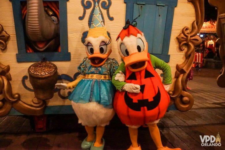 Foto dos personagens Donald e Margarida caracterizados com roupas de Halloween. O Donald está vestido de abóbora e a Margarida está com um vestido azul e dourado e um chapéu pontudo nas mesmas cores.