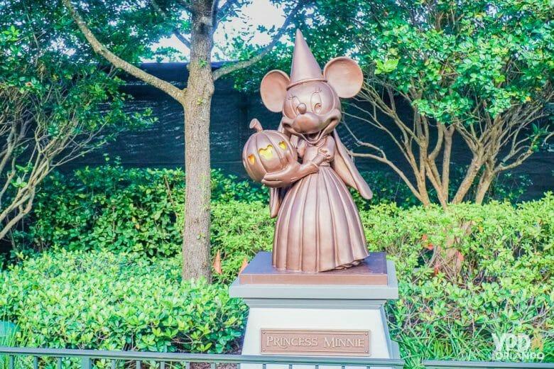 Foto de um dos detalhes temáticos da Festa de Halloween, uma escultura da Minnie vestida de bruxa, com chapéu pontudo e segurando a abóbora-carruagem da Cinderela.