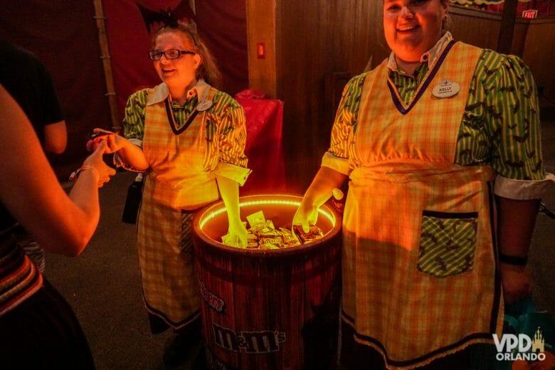 Dois funcionários da Disney distribuindo doces retirados de um barril iluminado por dentro com luz amarela.