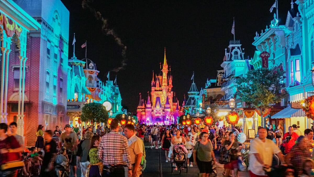 Imagem do Magic Kingdom com a decoração da Festa de Halloween, com as abóboras e o castelo iluminado ao fundo.