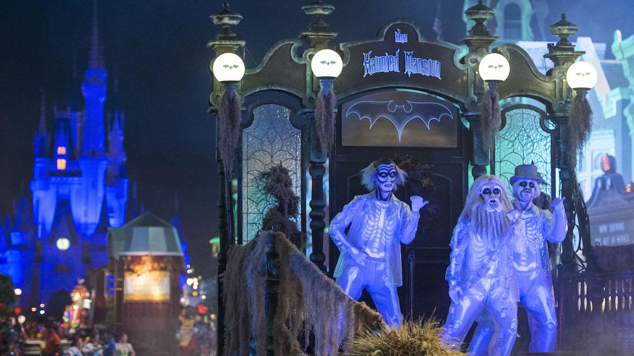 Imagem da parada especial de Halloween. Há três pessoas vestidas de esqueleto sobre o carro, iluminados por uma luz azul, e o castelo da Cinderela está ao fundo