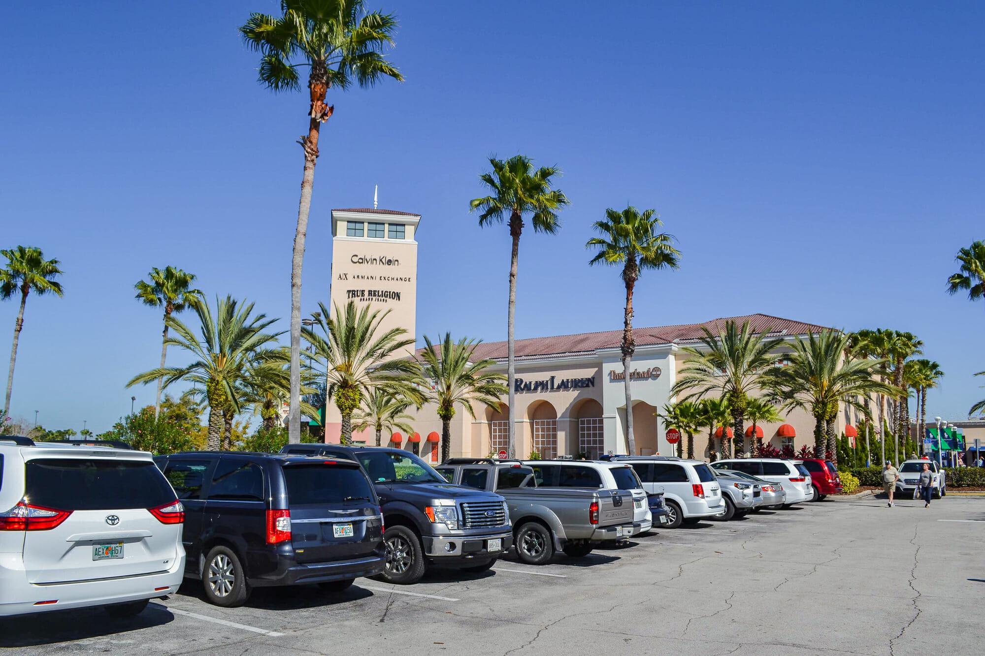 Imagem do estacionamento do Premium Outlet em Orlando, com carros enfileirados e o céu azul ao fundo.