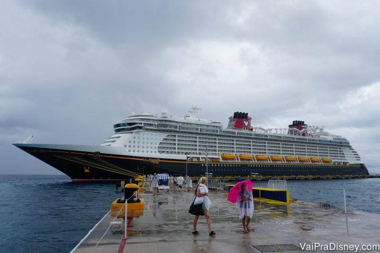 Foto do Disney Fantasy parado em Cozumel, com o céu nublado ao fundo.