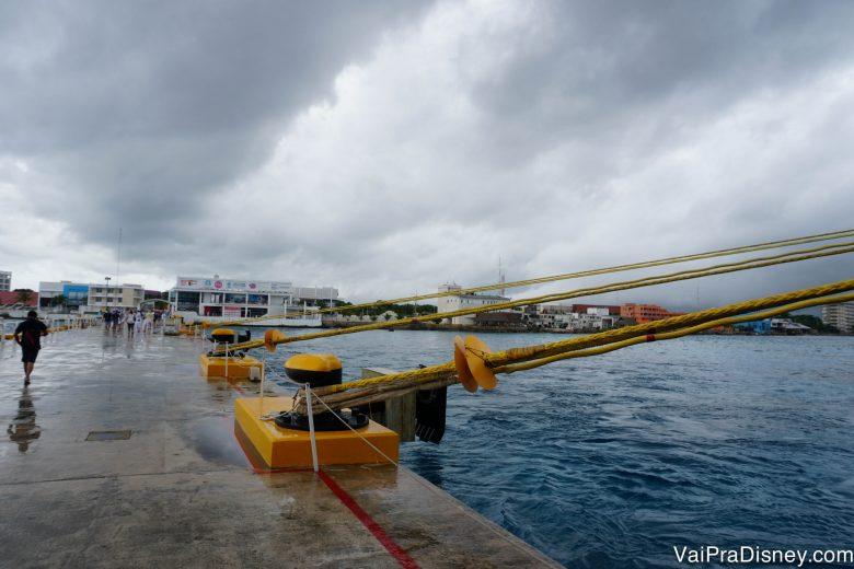 Foto do porto com o céu nublado e a chuva caindo durante a parada do Disney Fantasy em Cozumel