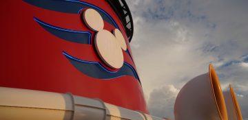 Foto de um detalhe do navio da Disney Cruise Line, o Disney Fantasy, com o Mickey em branco e o fundo pintado de azul e vermelho.