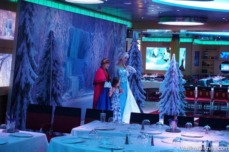 Foto da Elsa e da Anna de Frozen tirando foto com uma criança a bordo do Disney Fantasy