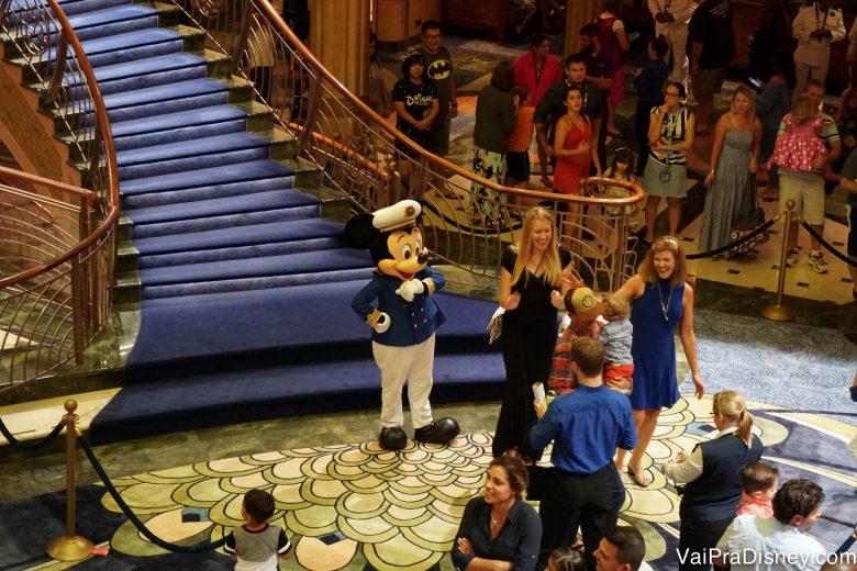 Foto do Mickey com roupa de capitão tirando foto com os visitantes no átrio do navio