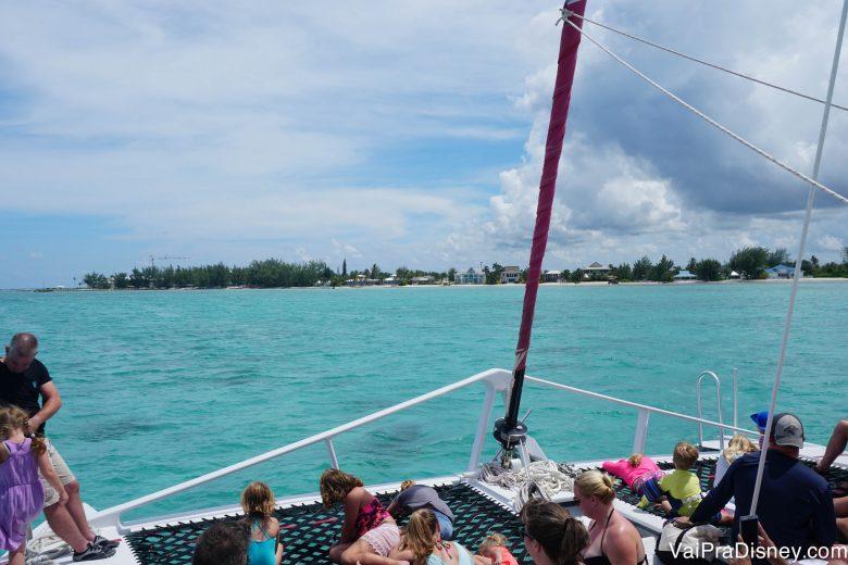 Foto dos visitantes a bordo do barco, com o mar verde-água e o céu limpo ao fundo