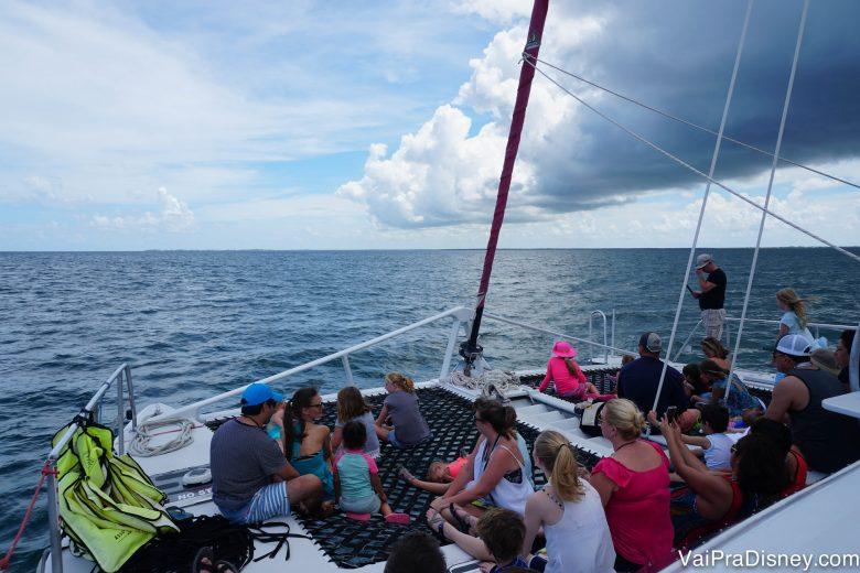 Foto dos visitantes no barco, com uma nuvem escura mas o céu já claro do outro lado.