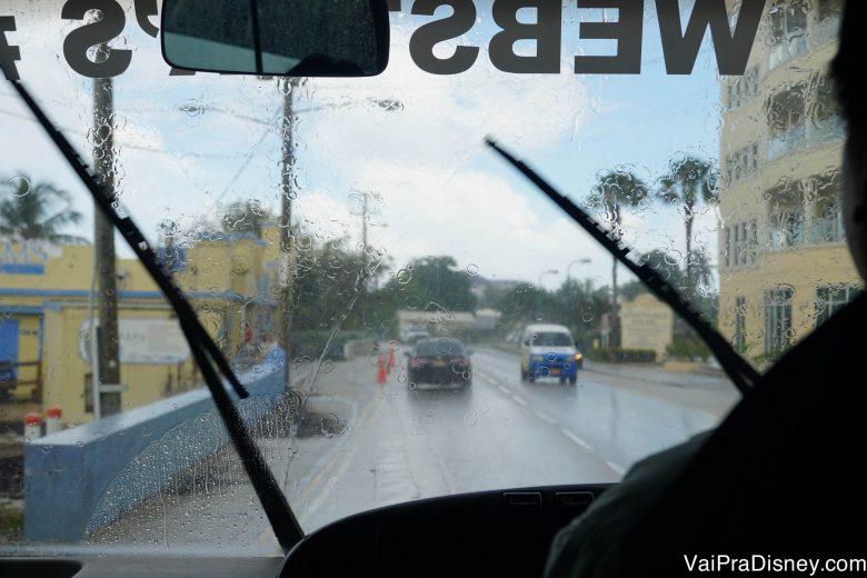 Foto da chuva na janela do ônibus, com a cidade visível através dela
