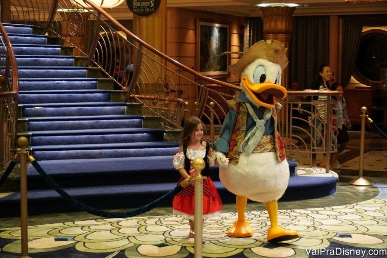 Foto do pato Donald vestido de pirata de mãos dadas com uma menininha durante o cruzeiro