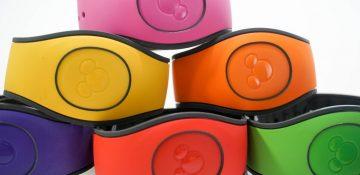 Foto de uma pilha de MagicBands da Disney nas cores rosa, amarela, laranja, vermelha e verde