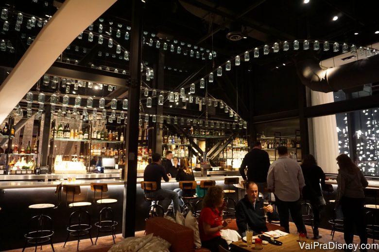 Foto da área do bar, com o mesmo estilo de decoração com lustres diferentes