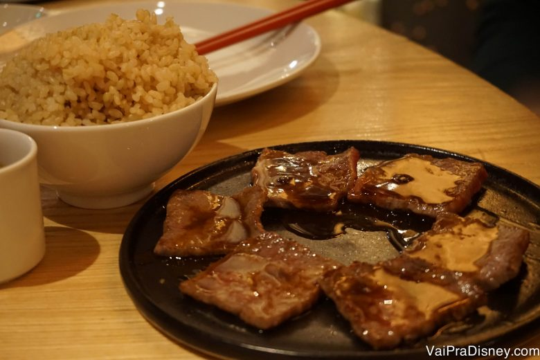 Foto de pedaços de carne sobre um prato e arroz em uma tigela ao lado