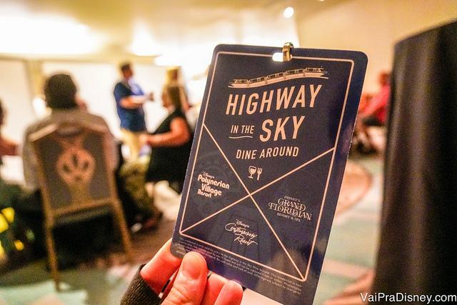 Foto de uma mão segurando o voucher do Highway in the Sky Dine Around, com um restaurante ao fundo
