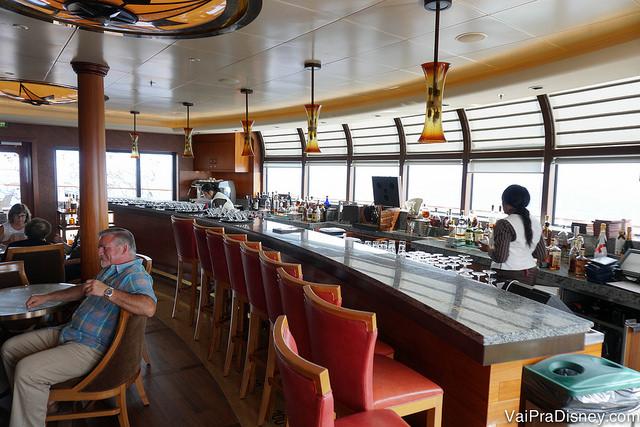 Foto do bar do restaurante Remy no navio, com cadeiras vermelhas e lustres alaranjados