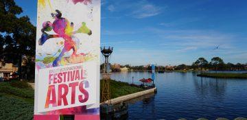 Foto do cartaz do Disney's Festival of the Arts no Epcot, mostrando um Mickey pintado em aquarela em várias cores, com o lago do parque ao fundo.