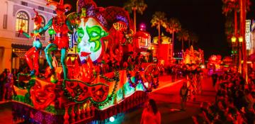 Foto da comemoração de Mardi Gras na Universal, com a parada passando pelo parque e a iluminação vermelha.