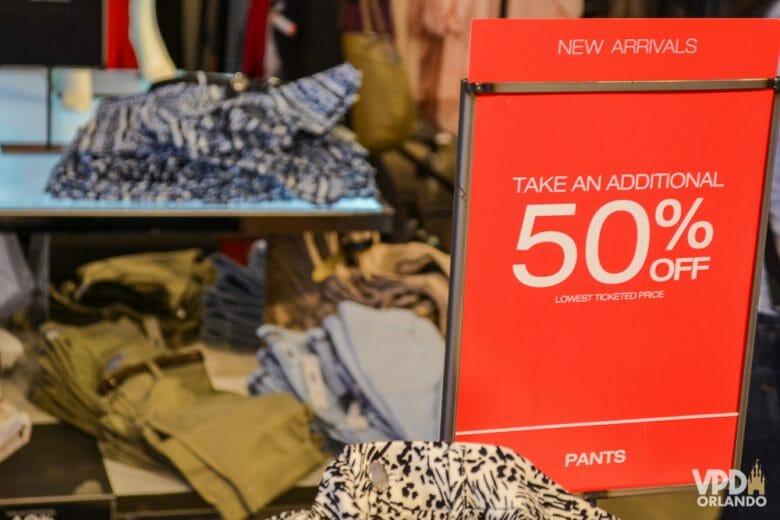 Várias promoções nos shoppings e principalmente nos outlets. Foto de uma placa vermelha anunciando 50% de desconto em um outlet de Orlando.