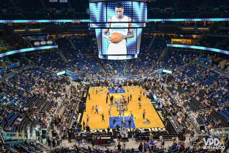 Fevereiro é um ótimo mês para curtir um jogo da NBA em Orlando. Foto do Amway Center durante um jogo da NBA. É possível ver a quadra, os jogadores e as arquibancadas.