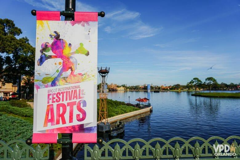 O Festival of the Arts acontece no Epcot! Foto do lago do Epcot com um pôster do Festival of the Arts, com um Mickey multicolorido em aquarela.