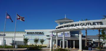 Foto do exterior do Premium Outlet de Tampa, todo pintado de branco e com o céu bem azul ao fundo