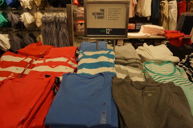 Foto de camisetas à venda no outlet por 12,99 dólares, em cores variadas