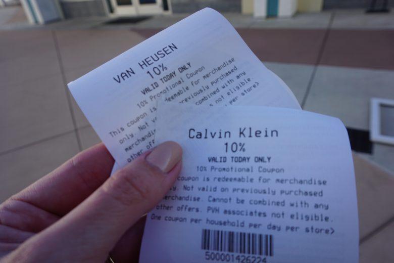 Foto de uma mão segurando cupons de desconto de 10% nas lojas Calvin Klein e Van Heusen
