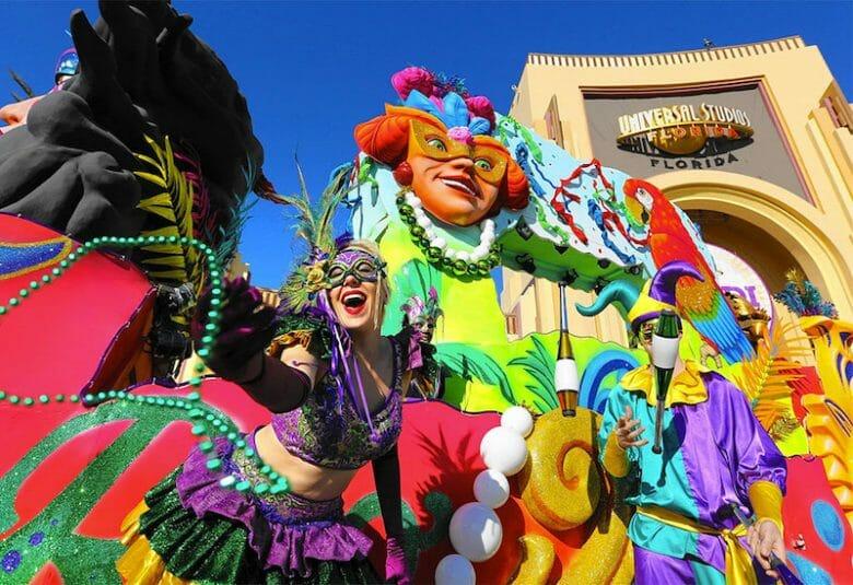 A imagem mostra várias pessoas fantasiadas com roupas e adereços bem coloridos, em frente ao arco da Universal. O Mardi Gras 2021 acontece entre fevereiro e março.
