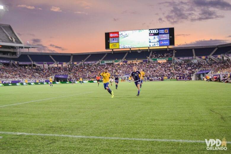 Em março começam as partidas de futebol do Orlando City! Foto do campo durante o jogo de futebol. É possível ver a arquibancada, o telão e alguns jogadores.