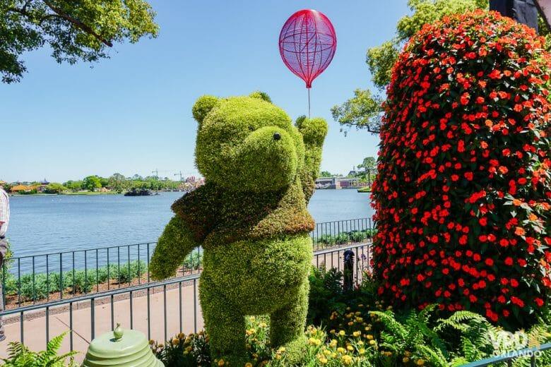 Em março começa o Flower & Garden Festival no Epcot. Foto de uma topiária do Pooh no Epcot, com o lago ao fundo e uma árvore florida ao lado.