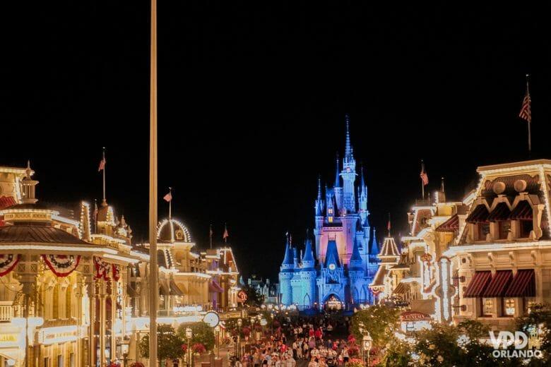 Os parques podem ficar mais cheios com o Spring Break! Foto do Castelo da Cinderela iluminado em azul e a Main Street do Magic Kingdom, cheia de pessoas e também iluminada.