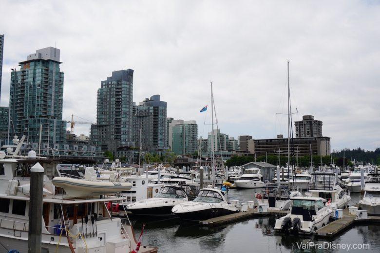 Foto de diversos barcos no porto de Vancouver, com os prédios da cidade ao fundo
