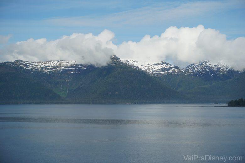 Foto da vista durante o cruzeiro, com as montanhas do Alaska, o mar e as nuvens