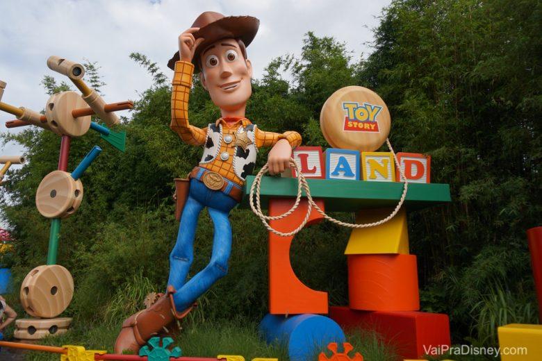 Foto do boneco gigante do Woody na Toy Story Land do Hollywood Studios, com os brinquedos que compõem o cenário ao seu lado.