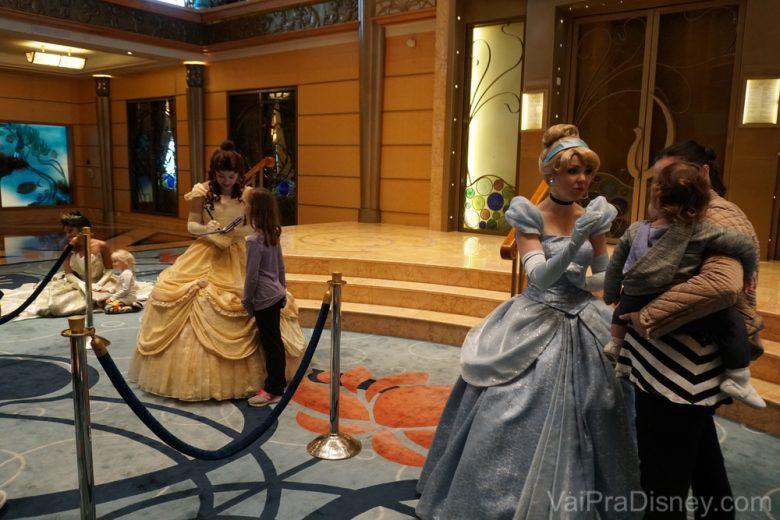 Foto da Cinderela e da Bela interagindo com visitantes no cruzeiro