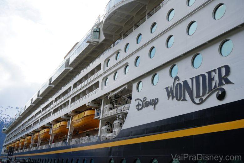 Foto do navio Disney Wonder, que faz parte da frota da Disney Cruise Line. É possível ver o nome do navio escrito em preto na lateral, as janelas redondas e detalhes em amarelo sobre a pintura. Ele faz o trajeto pelo Alaska